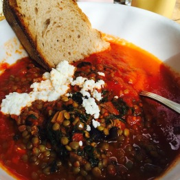 """Lentil Ragu - Swiss chard / feta cheese / country bread / two eggs poached - $12.5 - Ragu [rah-GOO] in Italian and ragoûte [ra-GOO] in French both come from the verb ragoûter meaning """"stimulate the appetite."""" Well this translation is lost in this hearty stew containing lentils instead of traditional ground beef or pork. This was filling as the lentils substantially increased the volume of the stew. The mixture of vegetables and sauce with the rich and tangy feta cheese was really good. I loved dipping the sourdough bread into the sauce to soak up all the flavors. The poached eggs get lost in this dish, literally. They are hidden under the ragu and with all the sauce and spices, they don't shine like they should at brunch. It's a great stew if you attend brunch later in the day. Earlier in the day I'd skip since the eggs are suppressed. Nice of them to create a vegetarian friendly ragu though."""